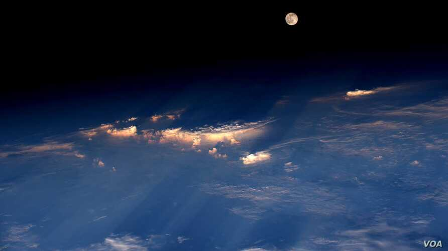 "Expedition 48 Commander Jeff Williams of NASA took this photograph on June 21, 2016, from the International Space Station, writing, ""A spectacular rise of the full moon just before sunset while flying over western China."""