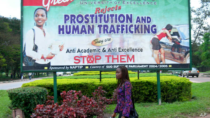 FILE - An unidentified student at Benin University walks past a billboard encouraging young women to fight against prostitution and human trafficking, on the university campus in Benin City, Nigeria on Sept. 9, 2006.