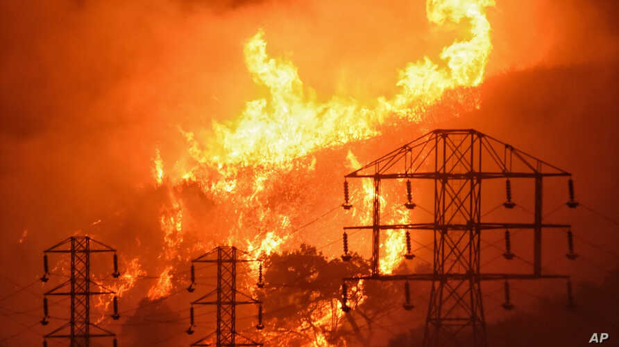 FILE - Flames burn near power lines in Sycamore Canyon near West Mountain Drive in Montecito, Calif., Dec. 16, 2017. The nation's largest utility, on Feb. 6, 2019, promised to overhaul its wildfire-prevention measures in response to its role in start