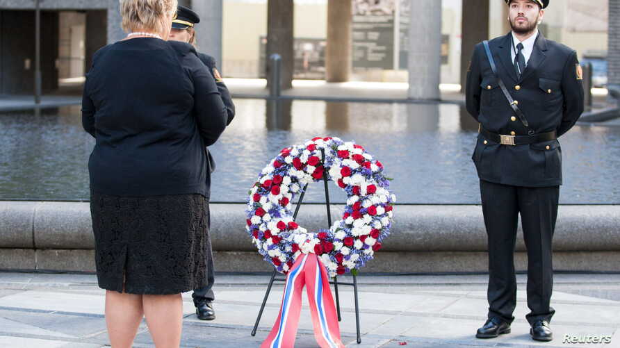Norway's Prime Minister Erna Solberg, left, attends a wreath-laying ceremony near the government building that was bombed four years ago by gunman Anders Behring Breivik in Oslo, July 22, 2015.
