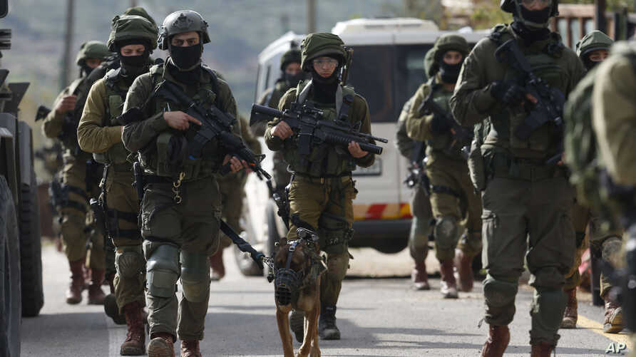 Israeli forces search for a Palestinian gunman in the village of Bruqin near the West Bank town of Salfit, Sunday, March 17, 2019. The Israeli military says a Palestinian killed an Israeli and seriously wounded two others in a West Bank shooting and