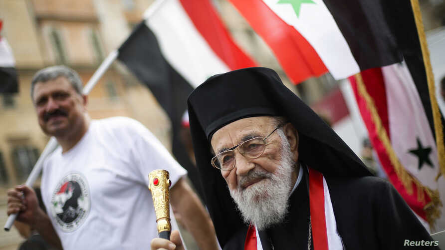 FILE - Hilarion Capucci of the Melkite Greek Catholic Church takes part in a rally in support of Syrian President Bashar al-Assad, in downtown Rome, Aug. 30, 2013.