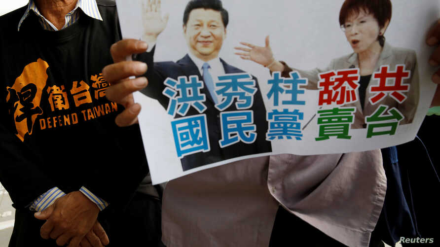 A pro-independence protester holds a sign with images of Nationalist Party, or Kuomintang (KMT), chairwoman Hung Hsiu-chu and China's President Xi Jinping during a protest against their meeting, at the airport in Taoyuan, Taiwan October 30, 2016.