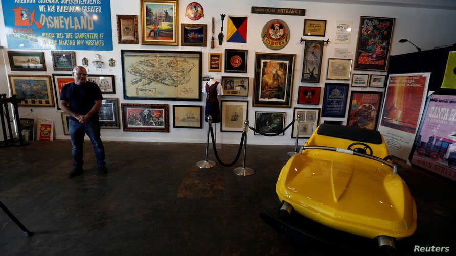 """Co-owner Mike Van Eaton stands next to a vehicle from the ride """"Autopia"""" and other items during a press preview for the upcoming auction """"Walt Disney's Disneyland"""" at Van Eaton Galleries in Sherman Oaks, California, June 1, 2017."""