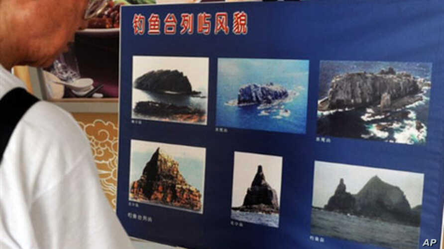 A man looks at photos showing the disputed island of Senkaku in Japan and Diaoyu in China during Diaoyu Island dispute conference in Chungho, Taipei county, 11 Sep 2010