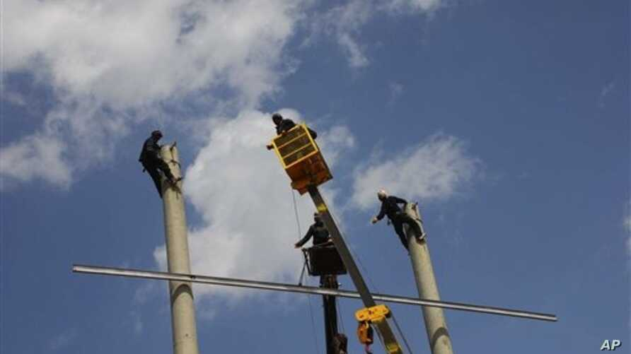 Afghans work on the construction of electricity poles, in the Robat-e-Sangi district, Herat province, west of Kabul, March 28, 2010.