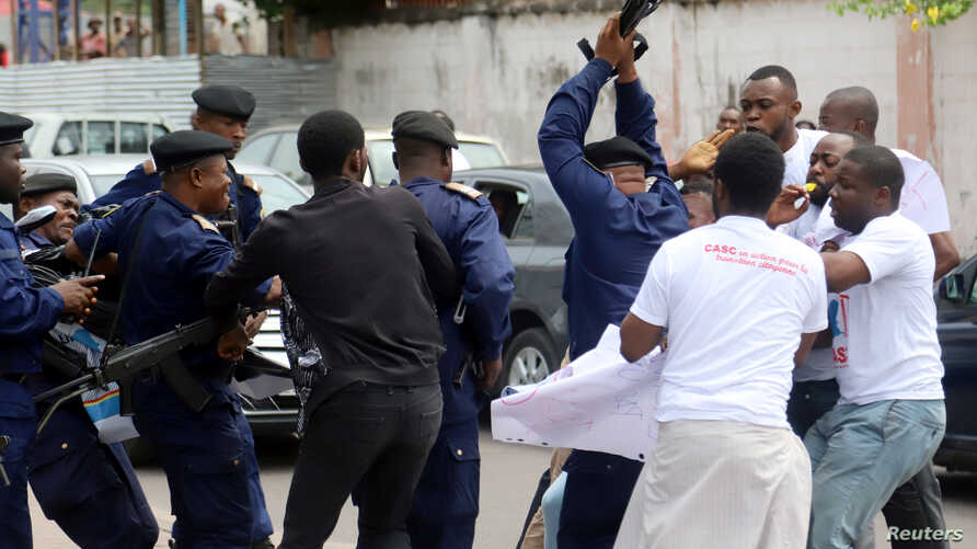 FILE - Congolese police officers attempt to disperse members of the Civil Society Action Collective (CASC) chanting slogans as they protest to demand free fair elections in Kinshasa, Democratic Republic of Congo, Sept. 19, 2018.