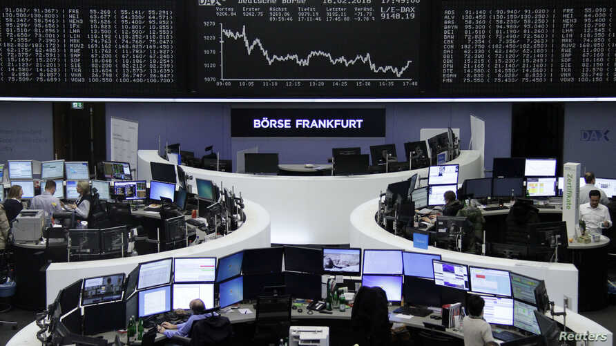 Traders work at their desks in front of the German share price index, DAX board, at the stock exchange in Frankfurt, Germany, Feb. 16, 2016.