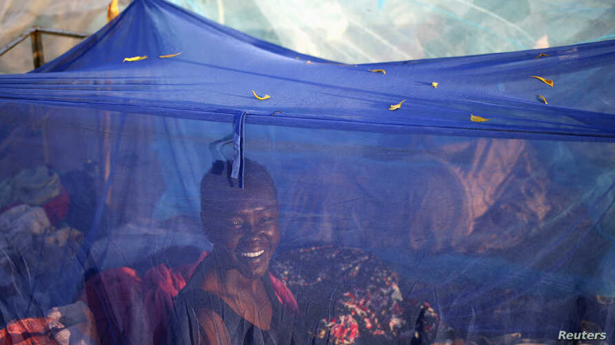 FILE - A woman sits inside a mosquito tent in the town of Abyei, Sudan.