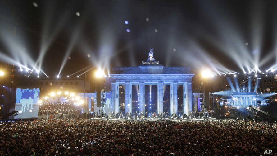 """Balloons of the art installation """"Lichtgrenze 2014"""" fly away in front of Brandenburg Gate during the central event commemorating the fall of the Wall in Berlin, Germany, Nov. 9, 2014."""