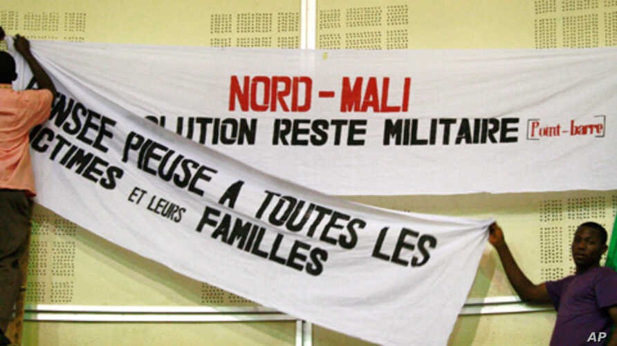 Workers at a meeting hall in Bamako, Mali, replace a banner that says 'The solution is military, period' for a forum, March 6, 2012.