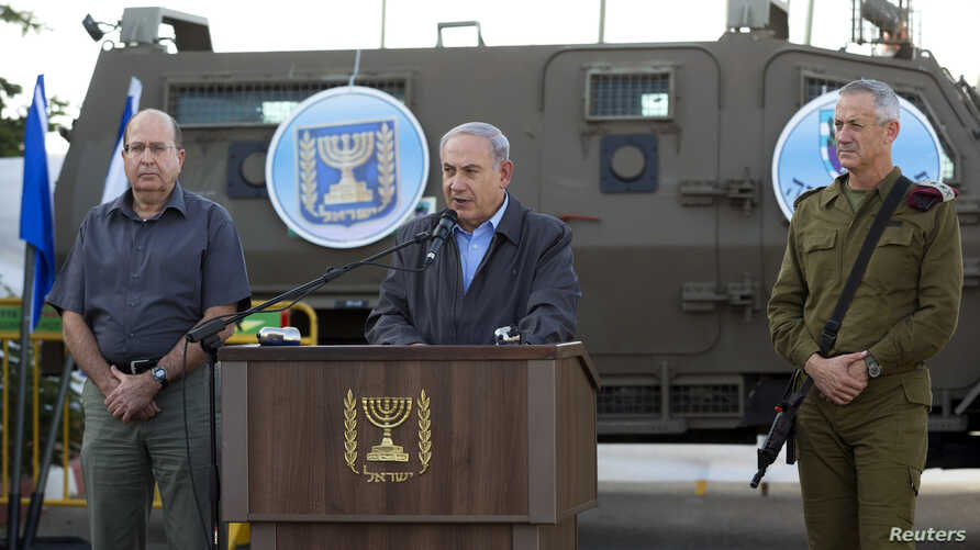 Israeli Prime Minister Benjamin Netanyahu (C) is flanked by Defense Minister Moshe Ya'alon (L) and Lieutenant-General Benny Gantz as he delivers a statement regarding an operation to locate three missing Israeli teenagers, at a military base near the