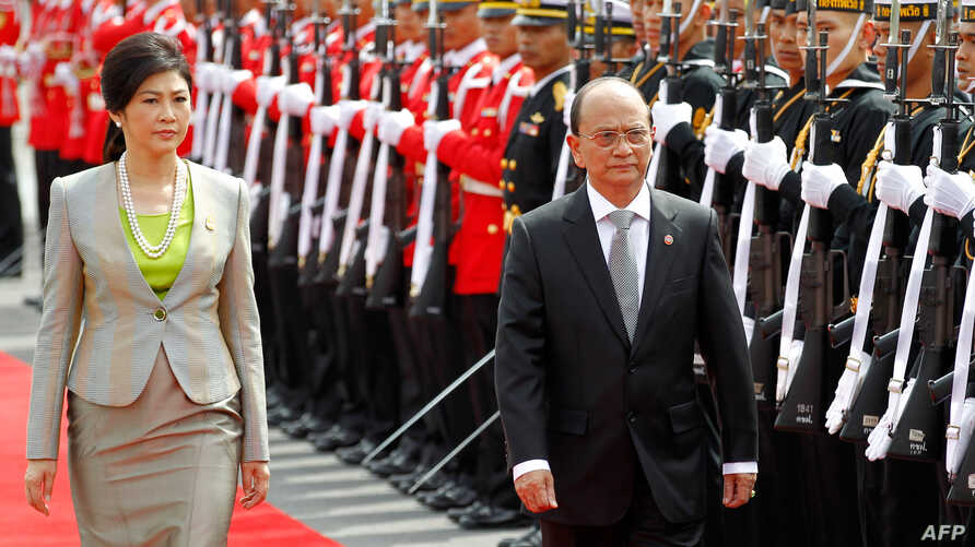 Burma President Thein Sein (R) and Thai Prime Minister Yingluck Shinawatra (L) review the honor guard during a welcoming ceremony at Government House in Bangkok, July 23, 2012.