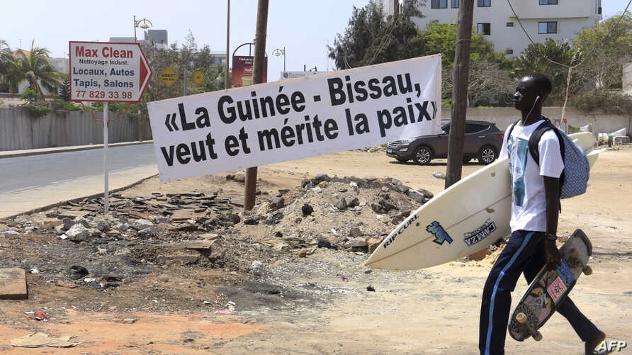 "FILE - A young man carrying a skateboard and a surfboard walks past a banner reading ""Guinea-Bissau wants and deserves peace,"" during an Economic Community of West African States (ECOWAS) summit in Dakar, Senegal, June 4, 2016."