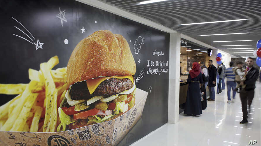 Palestinians buy fast food from the food court in the first indoor shopping mall in the Gaza Strip, in Gaza City, Feb. 18, 2017. In a welcome sign of normalcy, the mall - complete with an international retail chain, three-story bookstore and food cou