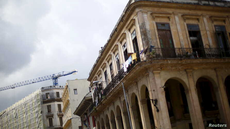 """FILE - A crane is seen behind an old building in Havana, Cuba, Sept. 18, 2015. As new constuction is booming in Cuba, European businesses may view a tougher U.S. policy toward Havana as """"an opportunity for them to step in,"""" a Cuba expert says."""