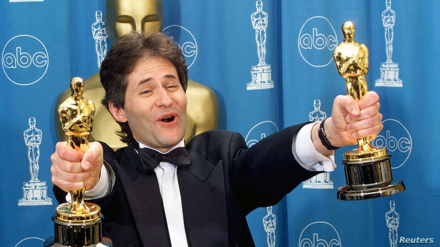 """James Horner holds up two Oscars after winning for Best Original Song and Original Dramatic Score for his work on the movie """"Titanic,"""" at the 70th Annual Academy Awards, March 23, 1998."""