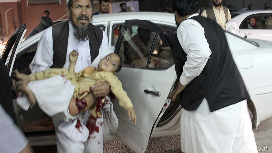 A man carries a wounded boy in a hospital, after a car bombing outside a sports stadium in Lashkargah, capital city of southern Helmand province, Afghanistan, March 23, 2018.