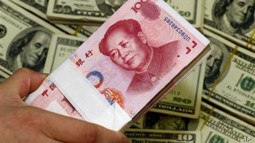 A pack of bills of Chinese yuan next to the U.S. currency