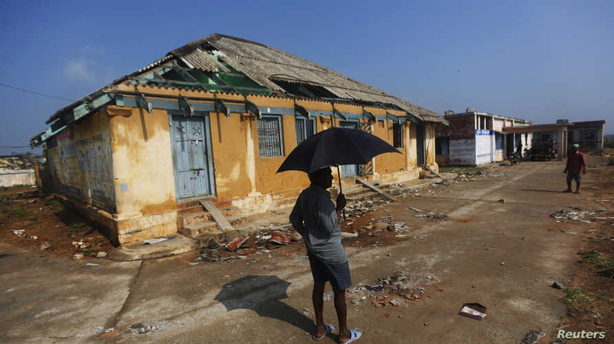 FILE - A man stands in front of a damaged house after Cyclone Phailin hit Gopalpur village, in Ganjam district in the eastern Indian state of Odisha, Oct. 14, 2013.