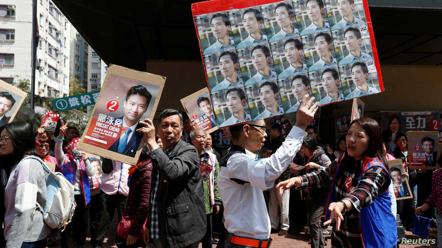 A supporter carrying photos of pro-democracy candidate Edward Yu walks past a supporter of Vincent Cheng from Democratic Alliance for the Betterment and Progress of Hong Kong, during a Legislative Council by-election in Hong Kong, March 11, 2018.