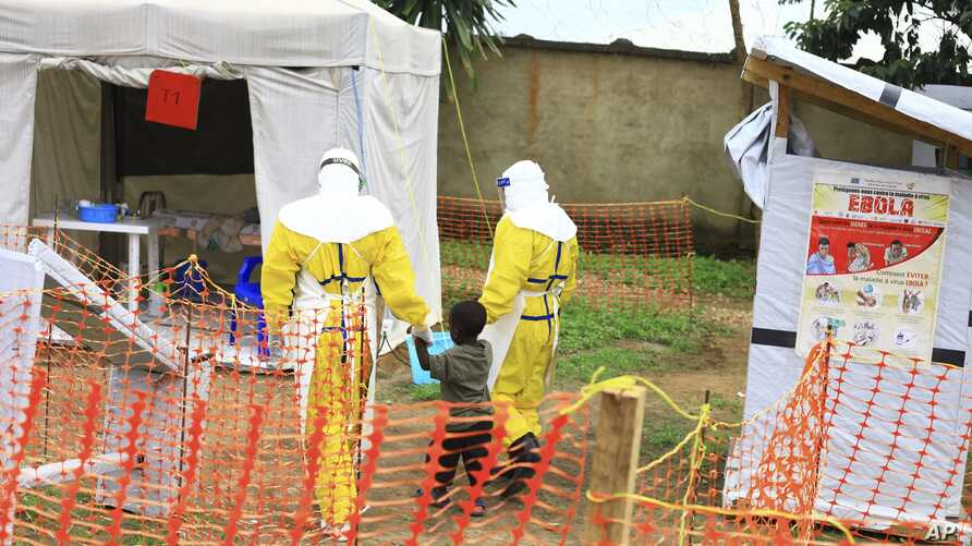 Photo taken Sept 9, 2018, shows health workers walking with a boy suspected of having the Ebola virus at an Ebola treatment centre in Beni, Eastern Congo.