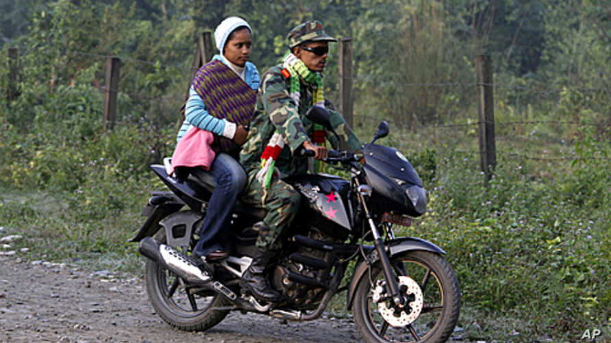 A former Maoist rebel rides a motorbike and arrives with his family for an integration program at Shaktikhor Cantonment in Chitwan, about 220 kilometers (140 miles) southwest of Katmandu, Nepal, November 19, 2011.