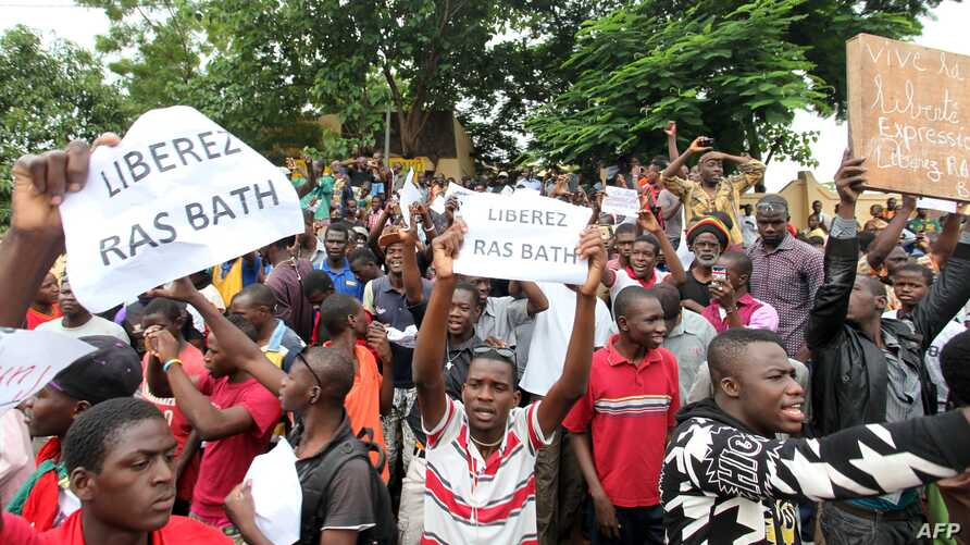"People hold placards reading ""Free Rasbath,"" a young radio presenter Mohamed Youssouf Bathily also known as ""Rasbath"" who was arrested two days ago, as they take part in a demonstration in front of Bamako's court in Mali, Aug. 17, 2016."