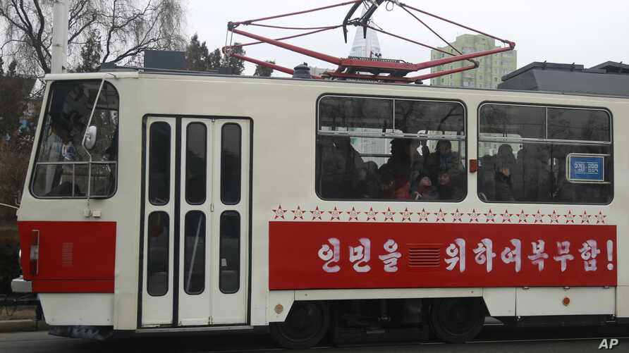 In this, Feb. 2, 2019 photo, people ride on a tram with red stars stenciled across its side in Pyongyang, North Korea. The red stars are awarded for every 50,000 kilometers (31,000 miles) driven without an accident.