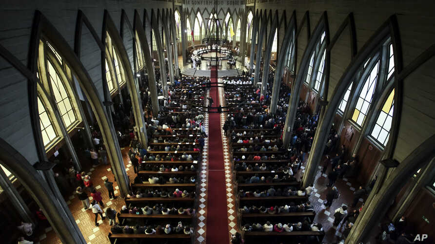 FILE - The Catholic Church officiates a reconciliation mass which seeks to bring together all sectors of the community that had become divided at the San Mateo cathedral of Osorno, Chile, June 17, 2018.