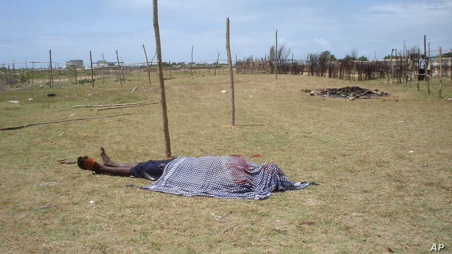 FILE - The lifeless body of a man is covered with a shroud as it lies in an open field in Kismayo, Somalia. Inter-clan violence killed six people Saturday in in Labi-Aano village, 45 km east of Dhuusamareeb, Somalia.