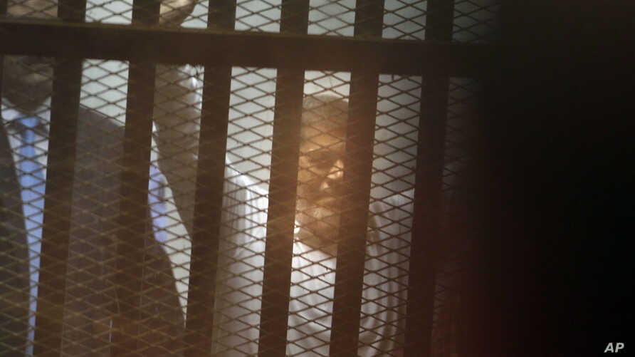 Egypt's ousted Islamist President Mohammed Morsi sits in a soundproof glass cage inside a makeshift courtroom at Egypt's national police academy in Cairo, Egypt, Tuesday, April 21, 2015. An Egyptian criminal court on Tuesday, sentenced Morsi to 20 ye