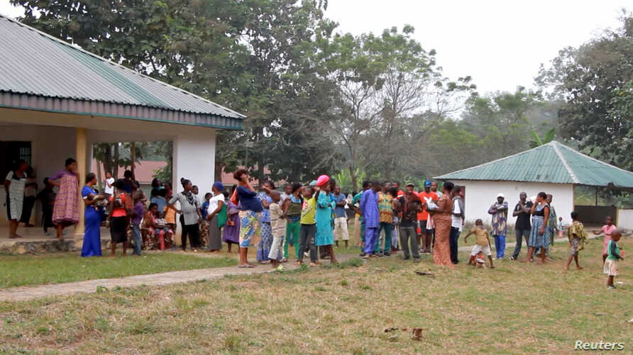 FILE - Cameroonian refugees stand outside a center in Agbokim Waterfalls village, which borders on Cameroon, in Nigeria, Dec. 9, 2017.