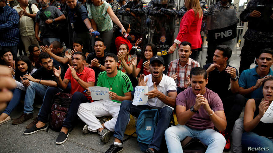 Mourners of the municipal lawmaker Fernando Alban shout slogans in front of riot police members standing outside the headquarters of Bolivarian National Intelligence Service (SEBIN) in Caracas, Venezuela, Oct. 8, 2018.