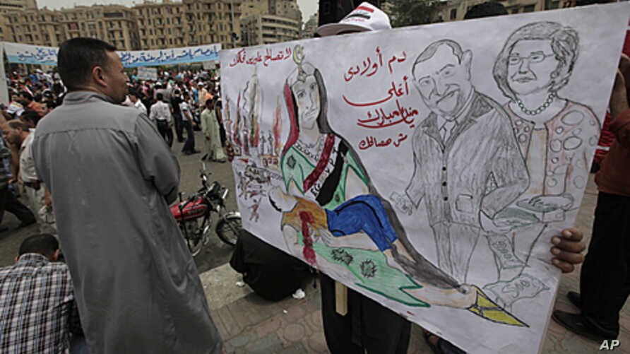 """An Egyptian protester carries a banner with drawings depicting ex president Mubarak and reads in Arabic """"No forgiveness, our children's blood is not cheap,"""" during a protest at Tahrir Square in Cairo, Egypt, May 27, 2011."""