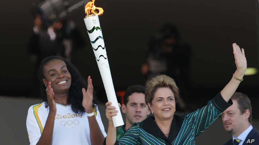 Brazil's President Dilma Rousseff, right, waves for people next to Olimpic Athlete Fabiana Claudino, during lighting ceremony of torch with the Olympic flame at Planalto Presidential Palace, in Brasilia, Brazil,Tuesday, May 3, 2016.