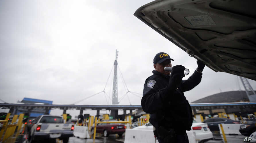 FILE  A U.S. Customs and Border Protection (CBP) officer checks under the hood of a car as it waits to enter the U.S. from Tijuana, Mexico through the San Ysidro port of entry in San Diego, Dec. 3, 2014.