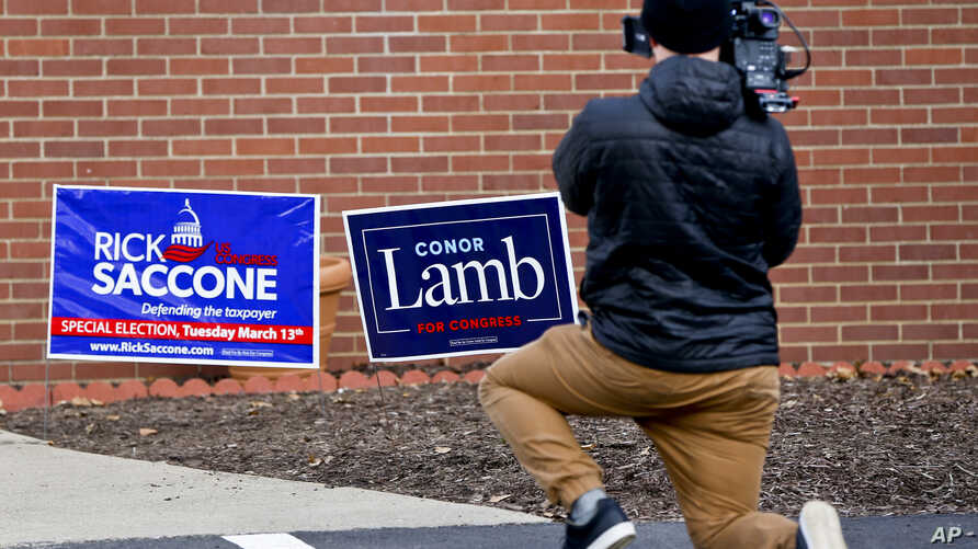 A cameraman films footage of campaign signs outside a polling place for the two candidates running in a special election being held for the Pennsylvania 18th Congressional District, in McKeesport, Pennsylvania, March 13, 2018.
