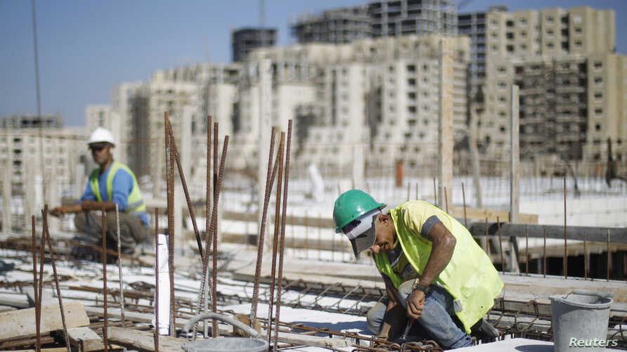 """FILE - Palestinian laborers work at a construction site in the new Palestinian town dubbed Rawabi or """"The Hills"""", near the West Bank city of Ramallah, Oct. 27, 2013."""