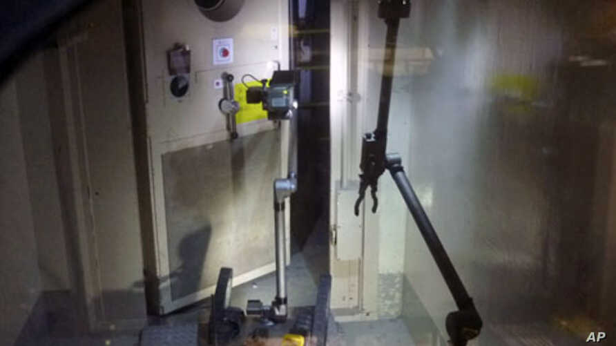 """A remote-controlled robot called """"Packbot"""", which has capabilities including maneuvering through buildings, taking images, and measuring radiation levels, opens a door at Tokyo Electric Power (TEPCO) Co.'s crippled Fukushima Daiichi Nuclear Power Pla"""