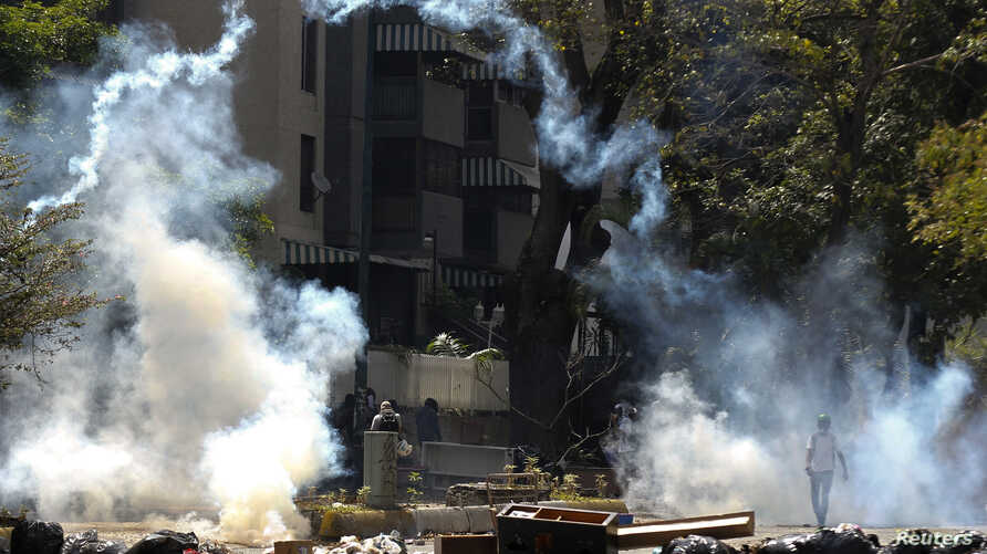 Anti-government protesters walk through tear gas during riots in Caracas, Apr. 6, 2014.