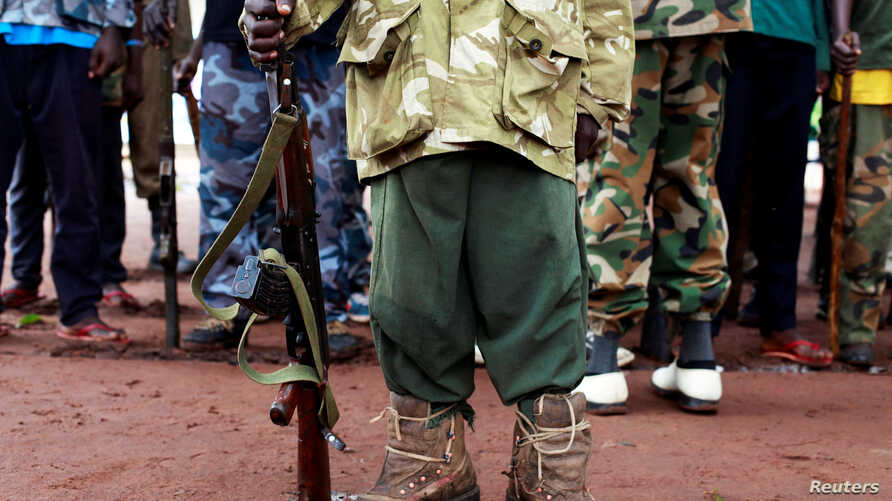 A former child soldier holds a gun as they participate in a child soldiers' release ceremony, outside Yambio, South Sudan.