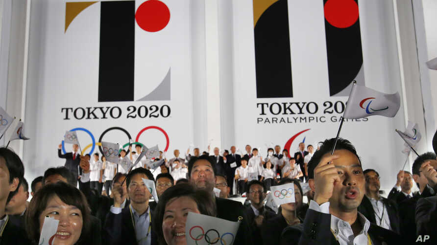 Visitors wave flags in front of the official emblems of the Tokyo 2020 Olympics and Paralympic Games at Tokyo Metropolitan Plaza in Tokyo, July 24, 2015..