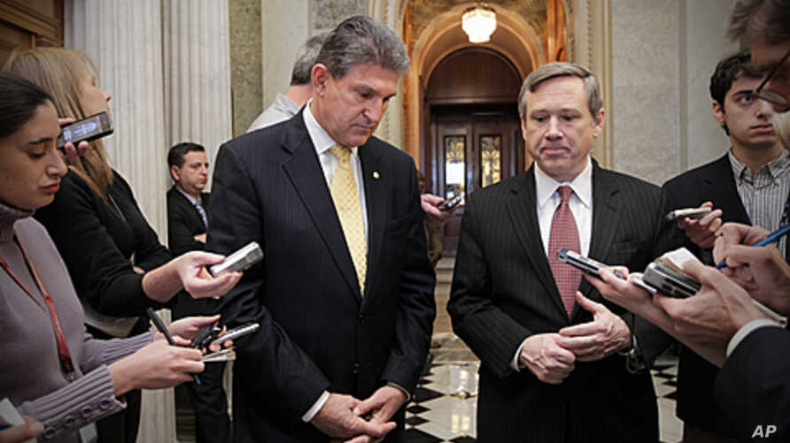 Senator Joe Manchin, left, and Senator Mark Kirk comment as the Senate approves legislation that extends Social Security payroll tax cuts for two months, at the Capitol in Washington, December 17, 2011.