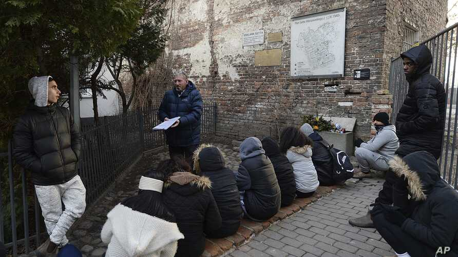 A group of college students from Israel being taught about Holocaust history at a fragment of the wall that isolated the Warsaw Ghetto and that a regional official wants to put on a list of protected historical monuments, in Warsaw, Poland, Tuesday,