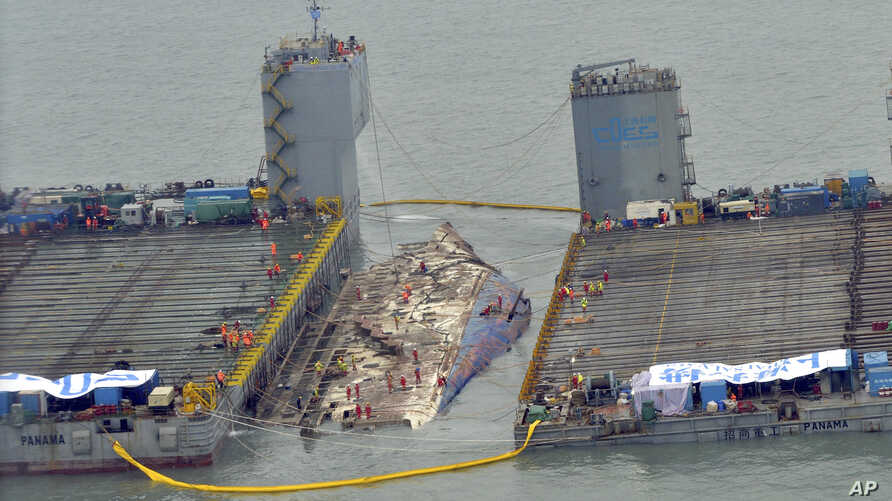 Workers prepare to lift the sunken Sewol ferry (center) in waters off Jindo, South Korea, March 23, 2017. The 6,800-ton South Korean ferry emerged from the water  Thursday, nearly three years after it capsized and sank into violent seas off the coun