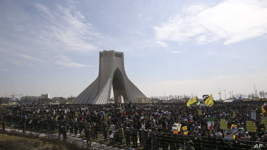 Iranians listen to speech of President Hassan Rouhani during a rally to commemorate the anniversary of the 1979 Islamic revolution under the Azadi (Freedom) monument tower in Tehran, Iran, Thursday,  Feb. 11, 2016.