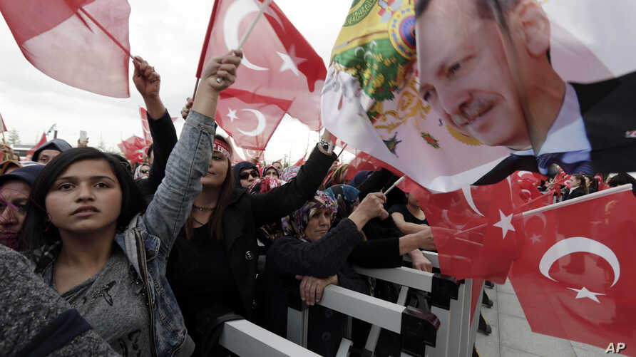 Supporters wave flags as Turkey's President Recep Tayyip Erdogan delivers a speech during a rally of supporters a day after the referendum, at his palace, in Ankara, April 17, 20