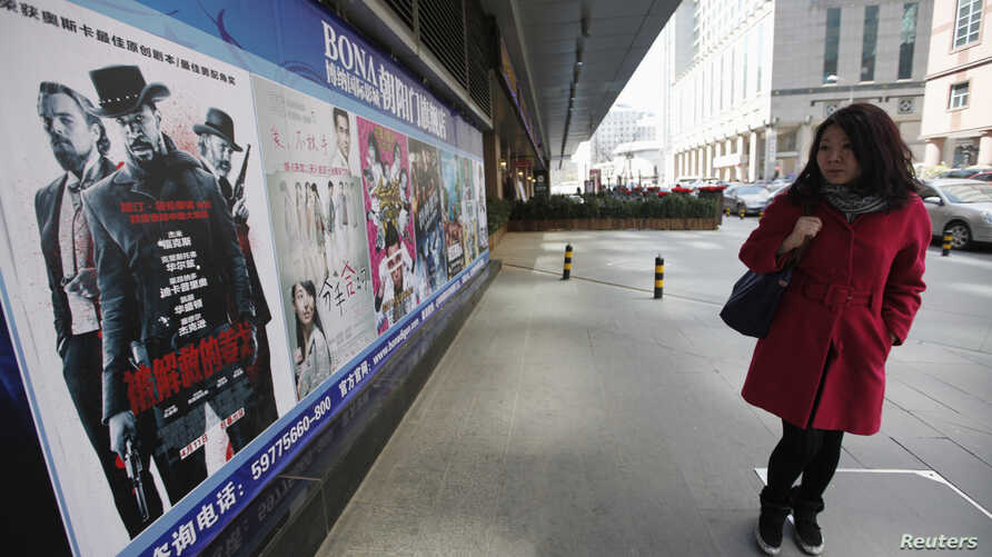 """A woman looks at a poster of the film """"Django Unchained"""" outside a cinema in Beijing, April 11, 2013."""