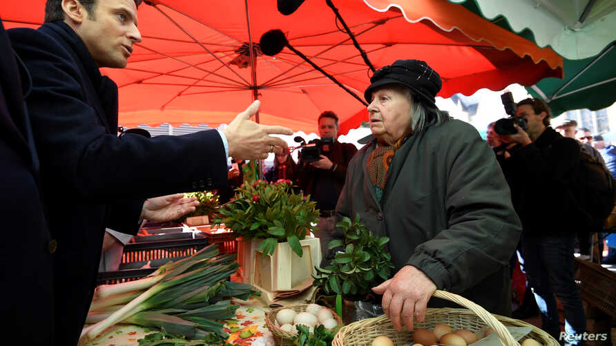 Emmanuel Macron (left), head of the political movement En Marche!, or Onward!, and candidate for the 2017 presidential election, visits a market as he campaigns in Poitiers, France, April 29, 2017.
